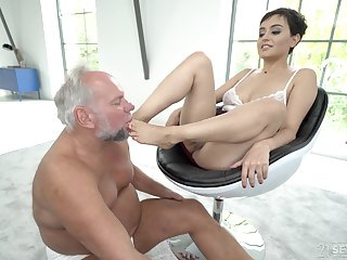 Short haired brunette babe Yasmeena has her feet licked by older guy