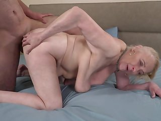 A big hairy dude is fucking a horny old granny on the bed